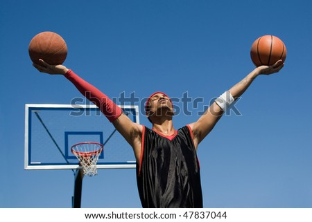 A young athletic build basketball player holding up two basketballs in the air.