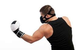 A young athletic man in a sports T-shirt, training black mask, boxing gloves performing uppercut on white isolated background
