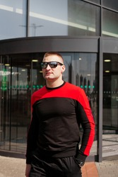 A young athletic man in a tracksuit walks out of the revolving doors