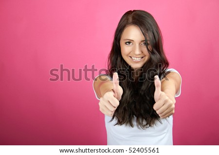 A young, attractive and happy woman is smiling with thumb up