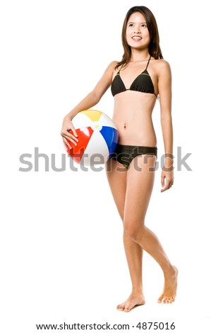 A young attractive Asian woman in a brown bikini holding a beach ball on white background