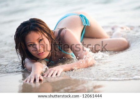 A young attractive asian woman lying on the beach near the sea