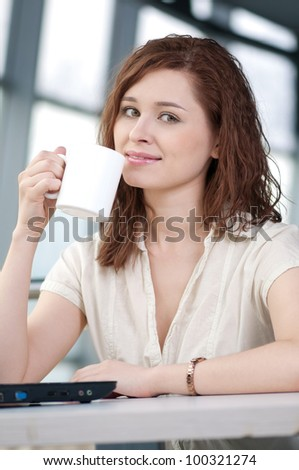A young attractive business woman sitting in a cafe with a laptop and coffee