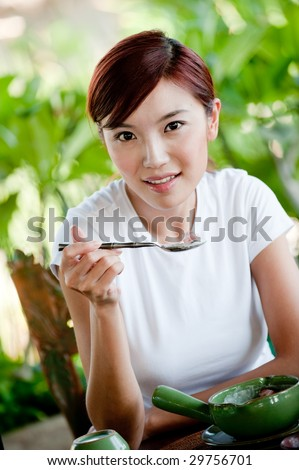 A young attractive Chinese woman eating fruit and yoghurt for breakfast at a tropical resort