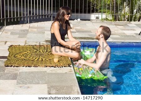 A young, attractive couple are beside and in the pool, staring. - horizontally framed