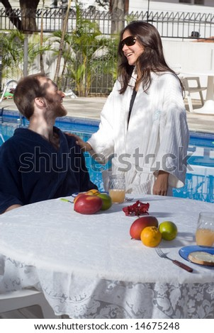 A young, attractive couple, the man sits down in a black robe, at a fruit covered table, the woman stands next to him in a white robe. - vertically framed - stock photo