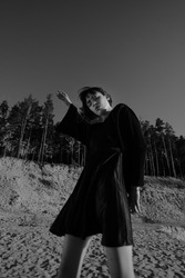 A young attractive dark-haired model girl posing and dancing in the pine forest in front of the sand quarry. Female model wearing black dress outdoors.