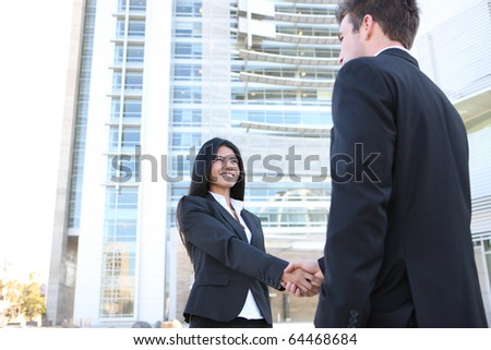 A young attractive diverse man and woman business team handshake at office