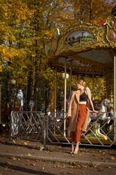 a young attractive European woman in a classic style of clothing in a beige coat and heels in autumn in an amusement Park professionally poses as a model