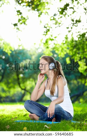 A young attractive girl listening to music in the park