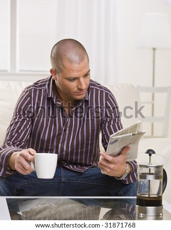 A young, attractive man is sitting at a coffee table, drinking coffee and reading a newspaper.  He is looking away from the camera.  Vertically framed shot.
