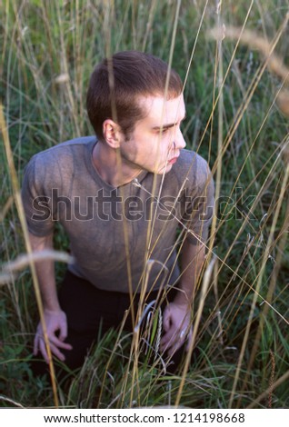 A young attractive man sitting in the grass of field on sunset. Side view portrait of a young Russian guy on nature background. #1214198668