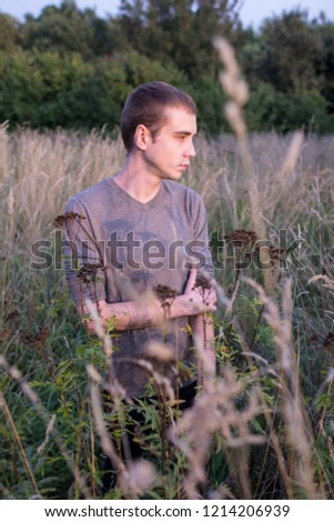 A young attractive thin guy standing in the tall grass on the forest background. A young student side view portrait in the park. #1214206939