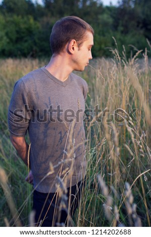 A young attractive thin guy standing in the tall grass on the forest background. A young student in the park. #1214202688