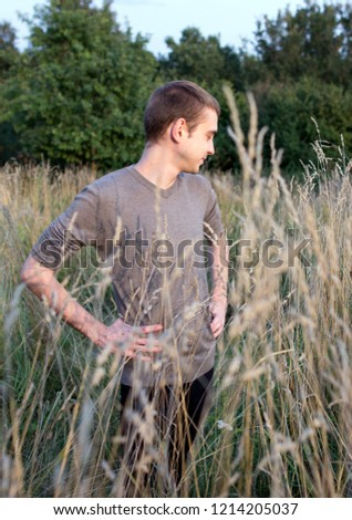 A young attractive thin guy standing in the tall grass on the forest background. A young student in the park. #1214205037