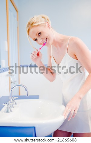 A young attractive woman brushing her teeth in the bathroom