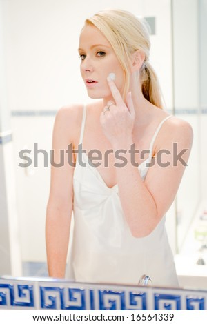 A young attractive woman in bathroom applying face cream