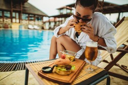 A young attractive woman on a vacation trying a tasty burger. Holliday, summer, and resort is the best thing I can do this weekend.
