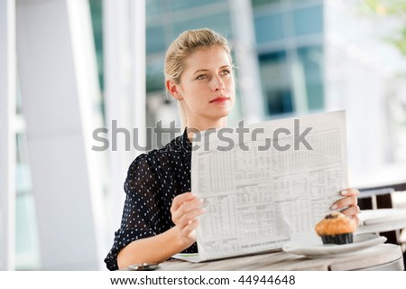 A young attractive woman reading newspapers at a cafeteria