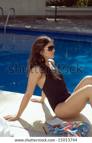 A young, attractive, woman, sits by the pool, relaxing. - vertically framed