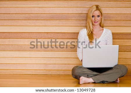 A young attractive woman using laptop and phone at home on wooden floor
