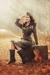 A young attractive woman with ringlets in Soviet-era military uniform is sitting on a vintage suitcase on the railway tracks with a brown antique violin.