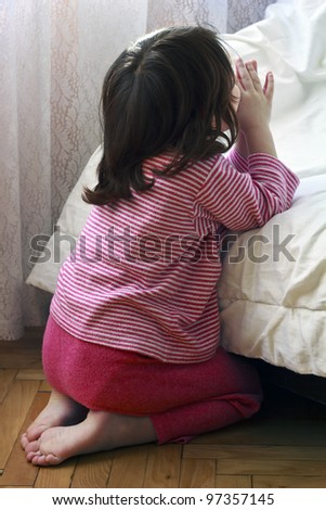 A young baby  girl saying her bedtime prayers.