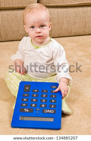 A young baby in a pair of generic pajamas sitting on the floor with a large, over-sized calculator.