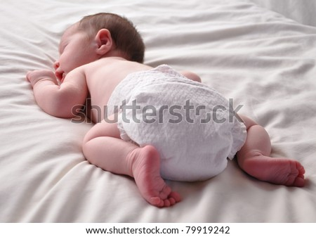 A young baby is sleeping on a bed with white sheets. The newborn is wearing a white diaper.