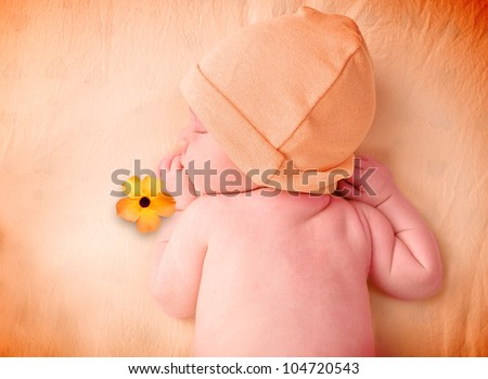 A young baby is sleeping on an orange bed sheet with a hat and flower. Use it for a love or time concept. - stock photo
