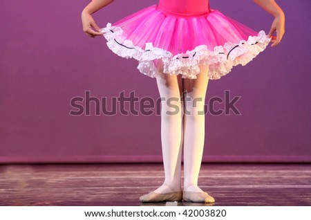 a young ballerina in first position rehearsing on stage
