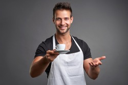 A young barista man smiling and offering a cup of coffee