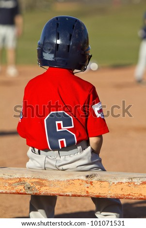 A young baseball player sitting on the bench