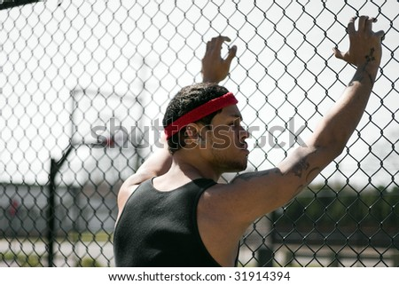 A young basketball leaning up against the chain linked fence at the basketball court.