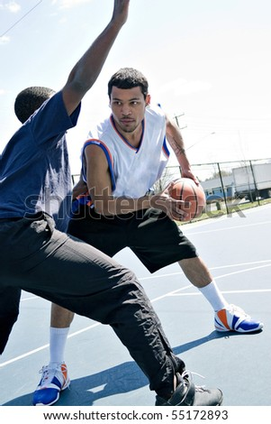 A young basketball player guarding his fierce opponent during a game of one on one at the park.