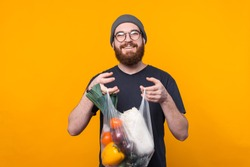 A young bearded and cheerful man is looking smiley at the camera and is holding a pouch with groceries