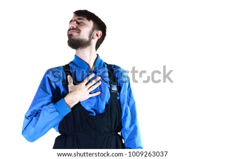 A young bearded guy in working uniform points to himself with his hand. A proud worker takes praise and encouragement to his person. Isolated on white
