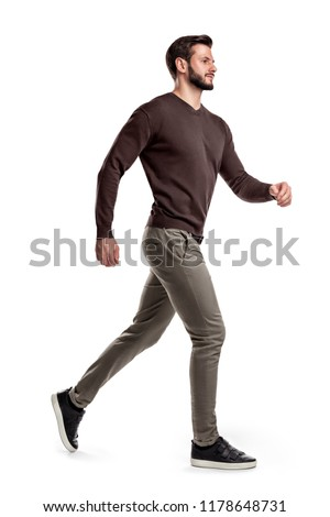 A young bearded man in a side view walks fast on the verge of running on a white background. Fast moving. Reaching goals. Getting close to success.