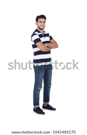A young bearded man standing with a crossed arms in a casual outfit, isolated on a white background. #1042489270