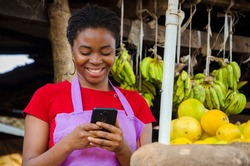 a young beautiful african market woman feeling happy about what she saw on her cellphone