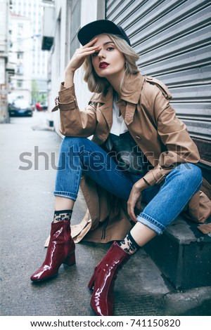 A young beautiful blonde woman is sitting and enjoying small urban street in Shanghai. She is wearing nice long brown coat and black hat. Her gorgeous face is accentuated by a dark red lipstick.