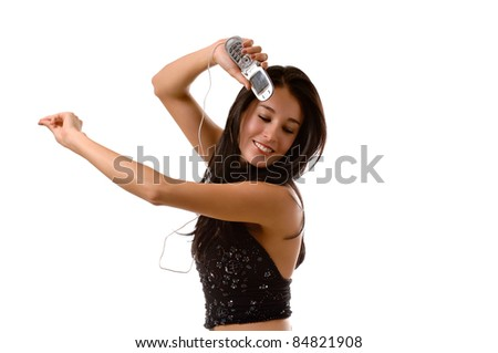 A young beautiful brunette woman, with her eyes closed listening to music on her cell phone.  She is dancing and snapping her fingers.