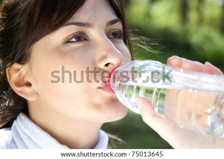 a young beautiful Caucasian girl drinks from bottle