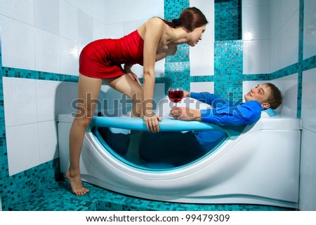 A young beautiful couple enjoying a bath with wine in a glass and looking at each other