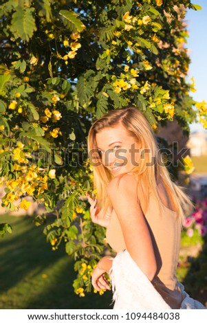 a young beautiful girl in beige dress is standing near tree smelling yellow flowers on it  enjoying ,relaxing on holiday in hotel in summer,looking at you #1094484038