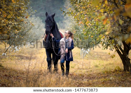 A young, beautiful girl on a walk with a horse in early autumn walks in the park.