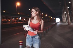 A young beautiful girl with a backpack behind her shoulders stands on the street near an airport or a railway station on a warm summer evening. She just arrived and waits for a taxi or her friends.