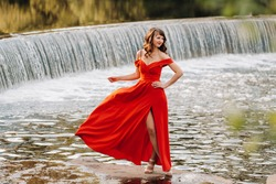 a young beautiful girl with long brown hair, in a long red dress with a ring around the lake