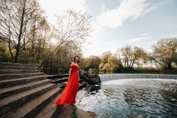 a young beautiful girl with long brown hair, in a long red dress with a ring around the lake.