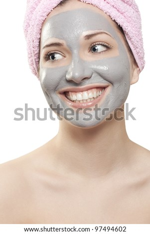A young beautiful girl with mud mask on face - stock photo